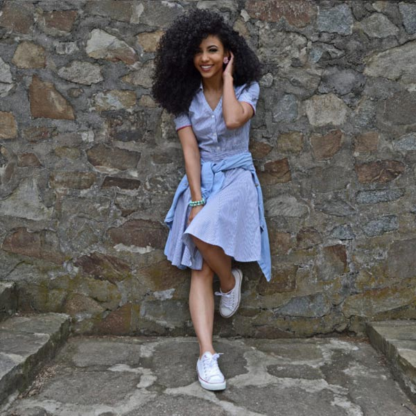 leaning pose against rock wall at Bryant park Charlotte in white chuck Taylor sneakers with after work outfit